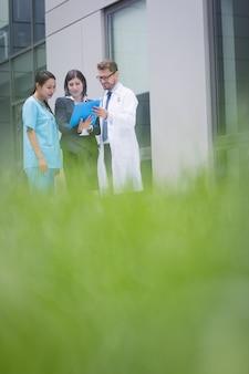 Médicos e enfermeira discutindo sobre o relatório