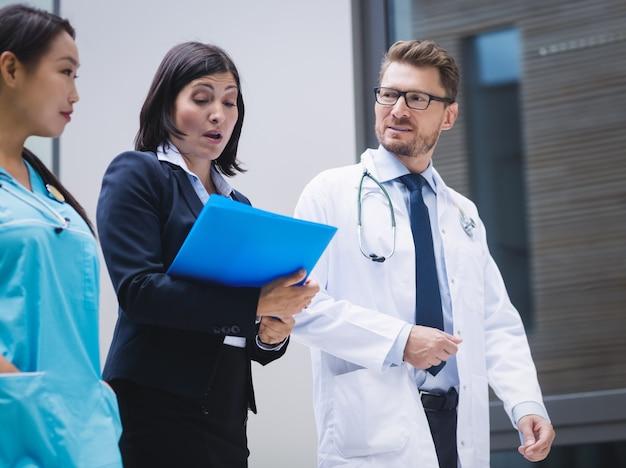 Médicos e enfermeiras interagindo enquanto caminham