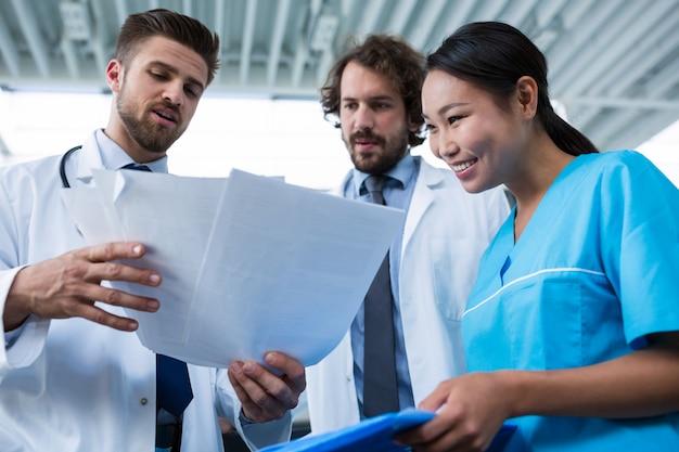 Médicos e enfermeiros discutindo relatórios médicos
