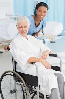 Médicos e paciente em cadeira de rodas