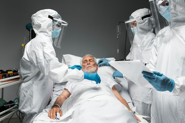Médicos e paciente infeccioso de perto