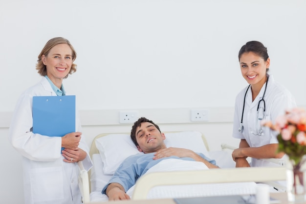 Médicos e paciente olhando para a câmera