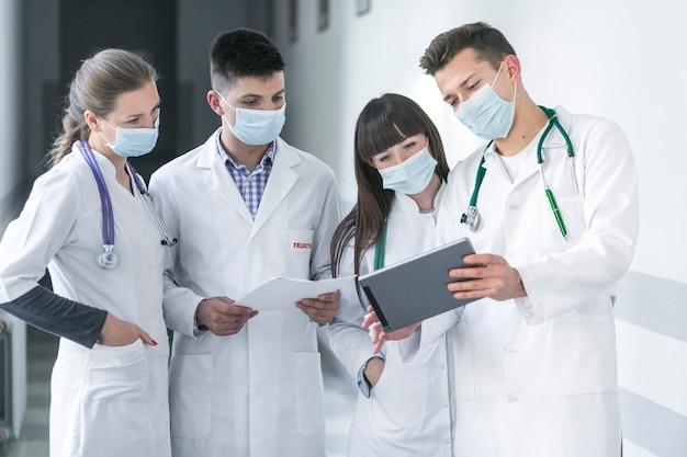 Médicos em máscaras usando o tablet