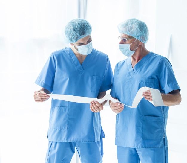 Médicos em scrubs lendo resultados de testes