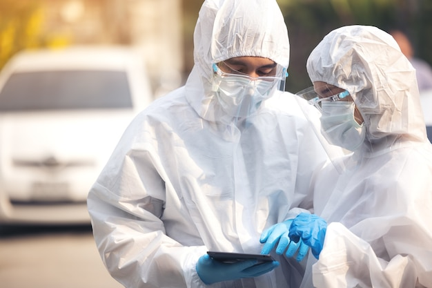 Médicos em terno de ppe usando tablet com protetor facial, discutindo em pé na rua