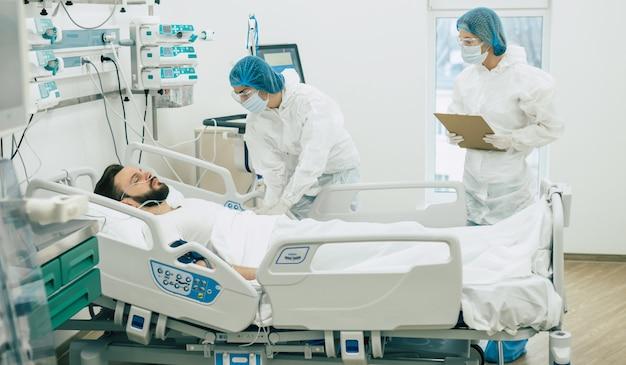 Médicos em trajes de proteção e máscaras estão examinando o jovem paciente infectado com coronavírus na enfermaria do hospital