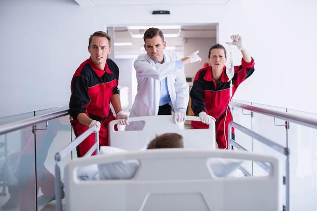 Médicos empurrando cama maca de emergência no corredor