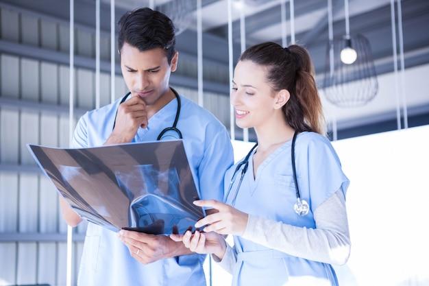 Médicos examinando relatório de machado no hospital