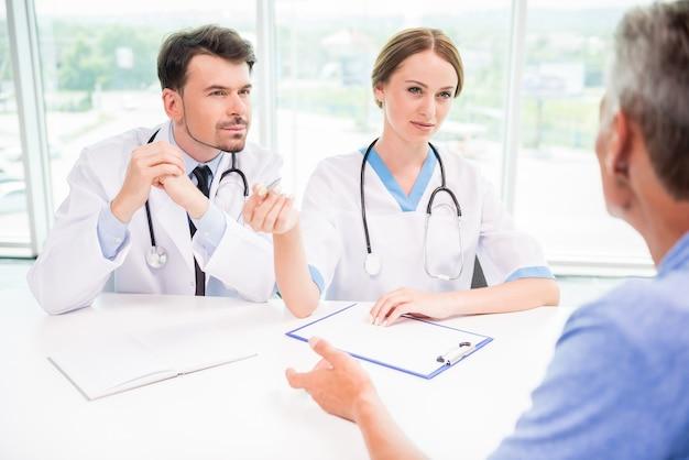 Médicos explicando o diagnóstico para amadurecer o paciente do sexo masculino.