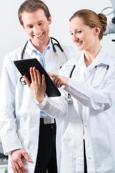 Médicos - homens e mulheres - discutindo relatórios de teste exibidos em seus computadores tablet