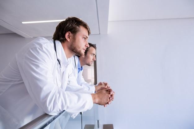 Médicos, inclinando-se sobre trilhos no corredor