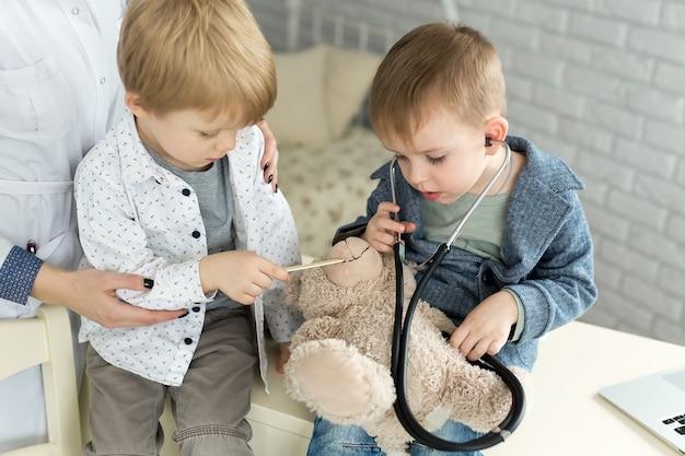 Médicos infantis brincam com um paciente de brinquedo