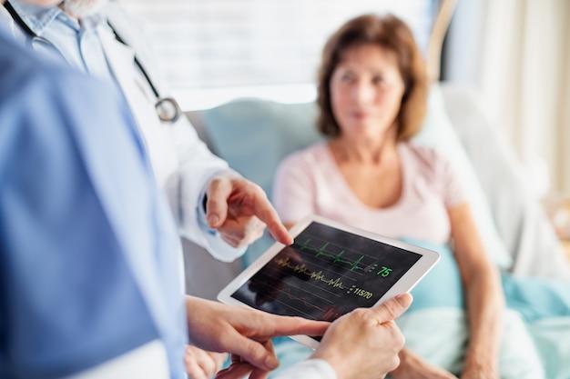 Médicos irreconhecíveis examinando uma paciente no hospital, barriga.