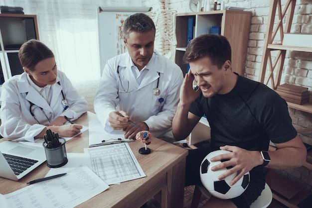 Médicos masculinos e femininos com estetoscópios no escritório com jogador de futebol.