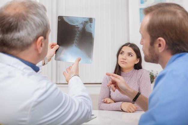 Médicos masculinos maduros que examinam a varredura de raios-x de um paciente