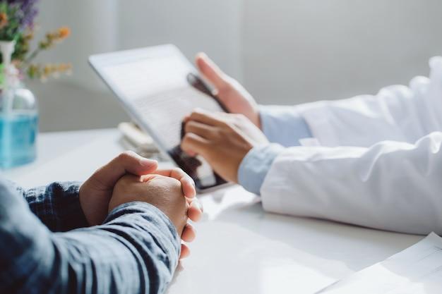 Médicos masculinos segurando o tablet digital enquanto discute e consulta o paciente. conceito de medicina e cuidados de saúde. médico e paciente
