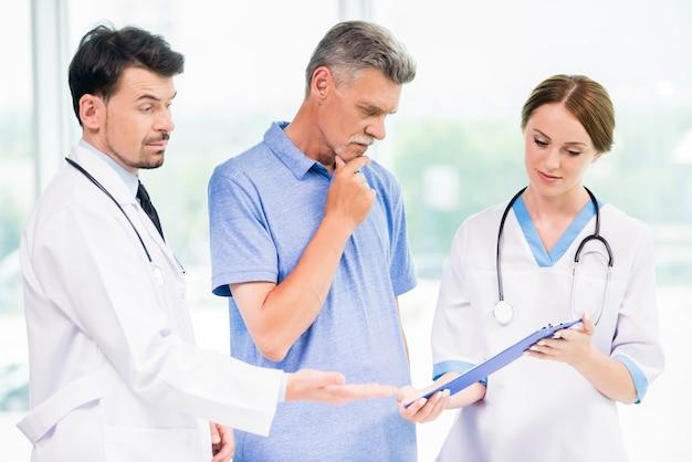 Médicos mostrando aos pacientes resultados de análise.