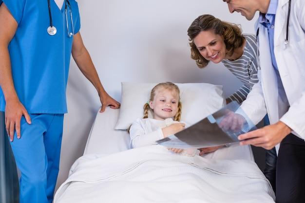 Médicos mostrando raios-x para paciente e mãe
