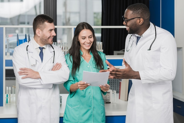 Médicos multiétnicos alegres com papéis