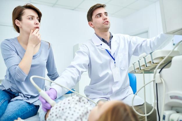 Médicos olhando seriamente para dispositivo médico