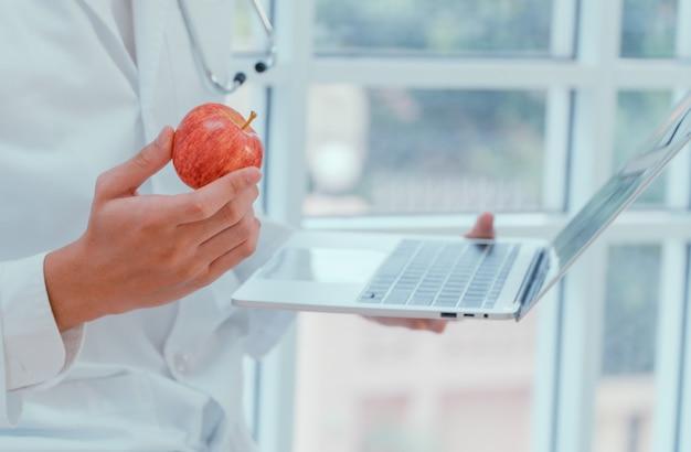 Médicos ou nutricionistas seguram maçãs e laptops na clínica para explicar os benefícios de frutas e legumes.