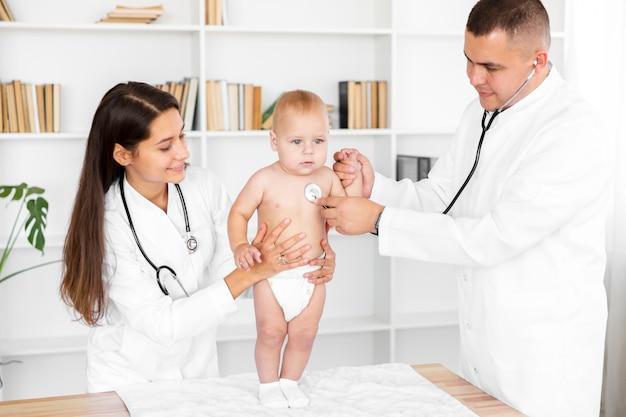 Médicos ouvindo adorável bebê com estetoscópio
