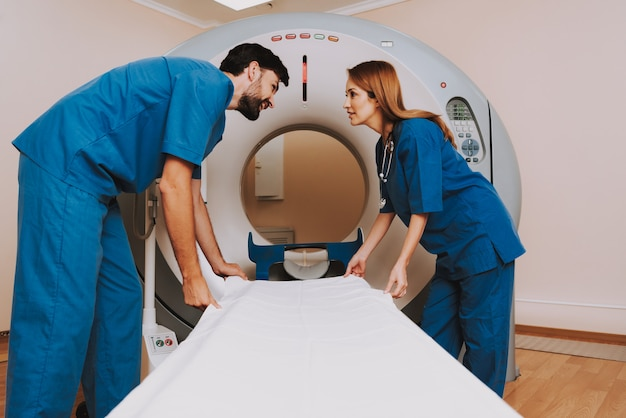 Médicos preparando tomógrafo para exame.