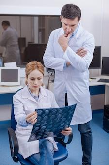 Médicos profissionais inteligentes e atenciosos olhando para a imagem de raio-x e pensando sobre o diagnóstico enquanto trabalham juntos