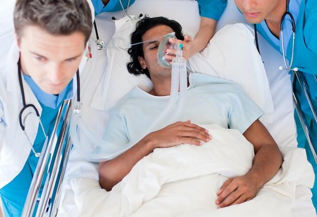 Médicos que transportam um paciente para unidade de terapia intensiva