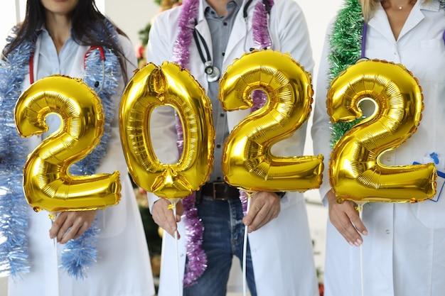 Médicos segurando balões dourados com números 2022 closeup. conceito de férias de natal para profissionais de saúde