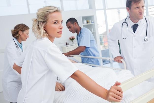 Médicos sérios prestes a andar com a cama do paciente