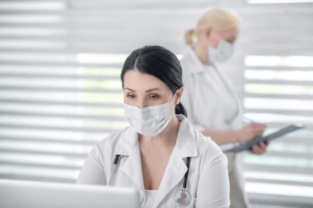 Médicos, trabalho. mulher morena com um estetoscópio em uma máscara protetora atrás de um laptop, colega de cabelos loiro em pé com uma pasta por trás, trabalhando atento.