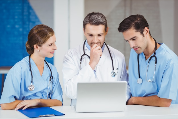 Médicos usando laptop em pé na mesa