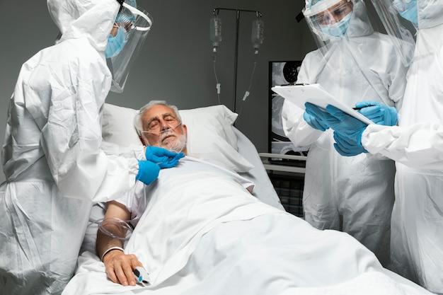 Médicos verificando paciente de perto
