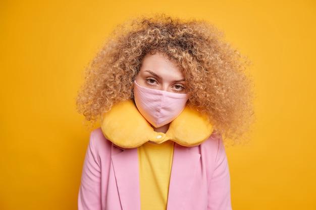 Medidas de segurança durante o surto de vírus. mulher séria parece usar máscara protetora para combinar com as poses de travesseiro de pescoço de roupa contra a parede amarela vívida. lockdown e covid 19