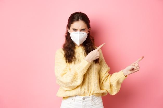 Medidas preventivas, conceito de saúde, mulher zangada, carrancuda e condenando algo ruim usando respirador de cobiçoso dedos apontando para o lado direito cópia espaço parede rosa
