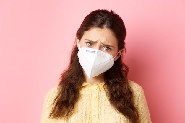 Medidas preventivas, conceito de saúde. perto da mulher jovem triste em respirador médico, expresse compaixão, olhe com pena e cara triste, de pé contra a parede rosa.