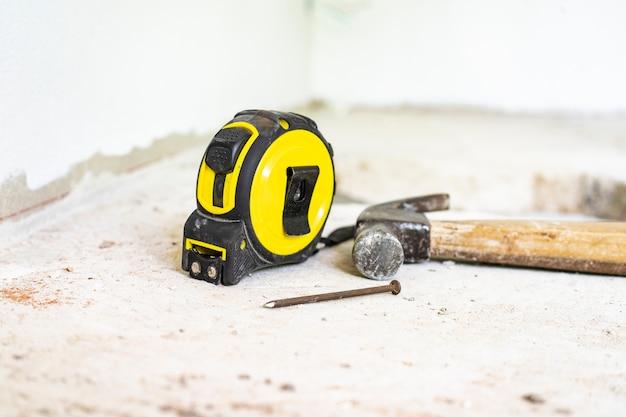 Medidor amarelo e martelo de aço têm unhas colocadas no chão de cimento.