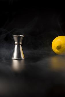 Medidor de coquetel entre fumaça e um limão no fundo