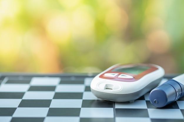 Medidor de glicose e lanceta para verificar o nível de açúcar no sangue no tabuleiro de xadrez.