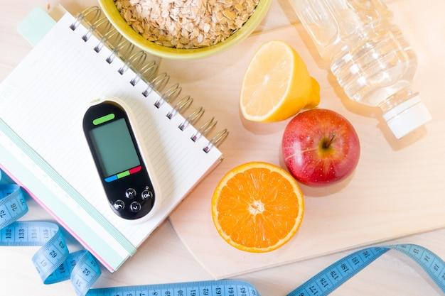 Medidor de glicose em um bloco de notas, tigela de mingau de aveia, fita métrica, frutas, uma garrafa de água em uma mesa de madeira