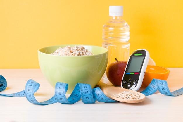 Medidor de glicose, garrafa de água, frutas, uma tigela de mingau de aveia e uma fita métrica azul sobre a mesa