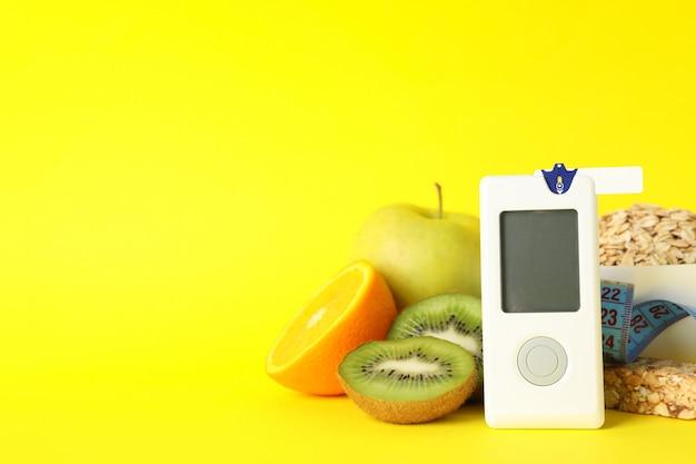 Medidor de glicose no sangue e alimentos para diabéticos na mesa amarela