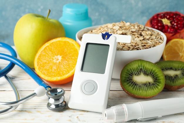 Medidor de glicose no sangue e alimentos para diabéticos na mesa de madeira