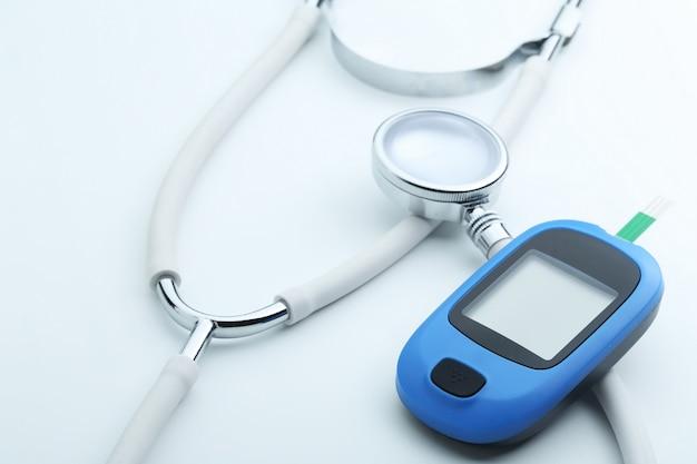 Medidor de glicose no sangue e estetoscópio no fundo branco
