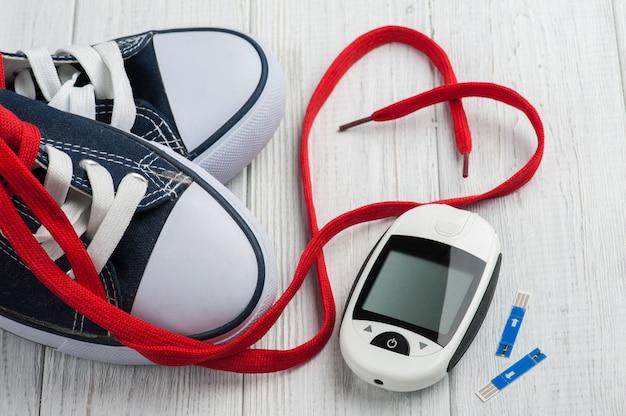 Medidor de glicose, sapatos desportivos, coração vermelho