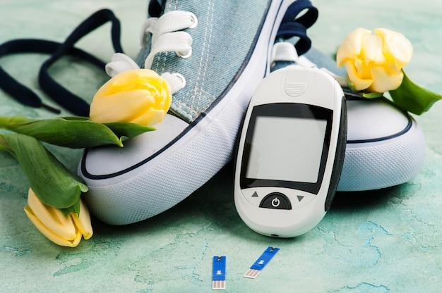 Medidor de glicose, sapatos desportivos e tulipas