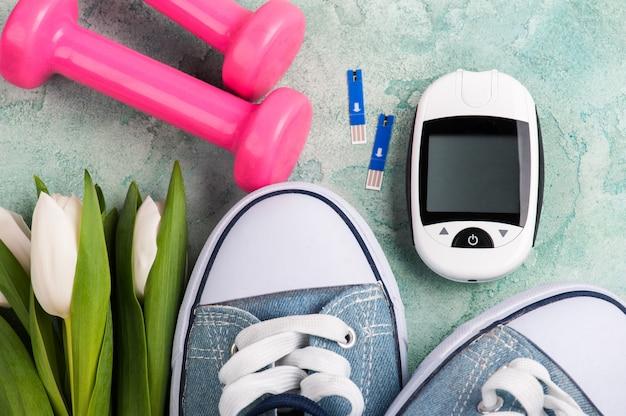 Medidor de glicose, sapatos desportivos, halteres rosa