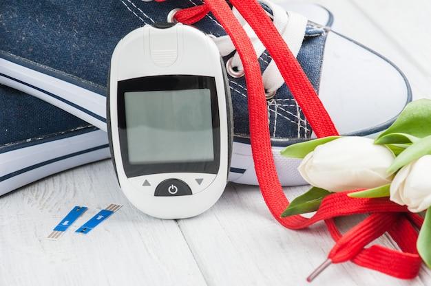 Medidor de glicose, sapatos desportivos, tulipas