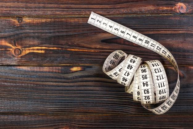 Medidor de indumentária e tesoura na madeira velha